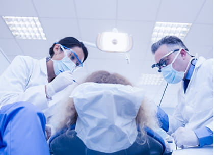 Two dentists treating patient