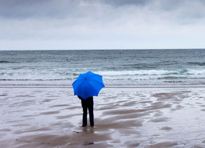 Person holding umbrella looking at stormy sea