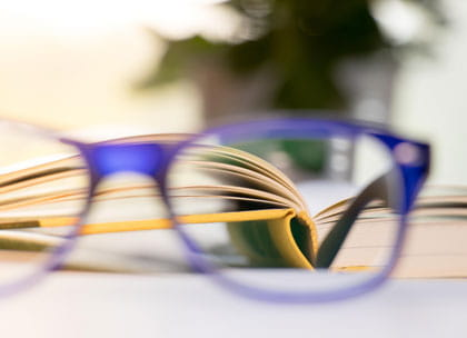 Glasses against blurred book in background